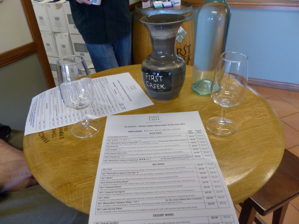 Tisch mit Weingläsern, Weinflasche und Papier mit der Auflistung der zu probierenden Weine + Preise