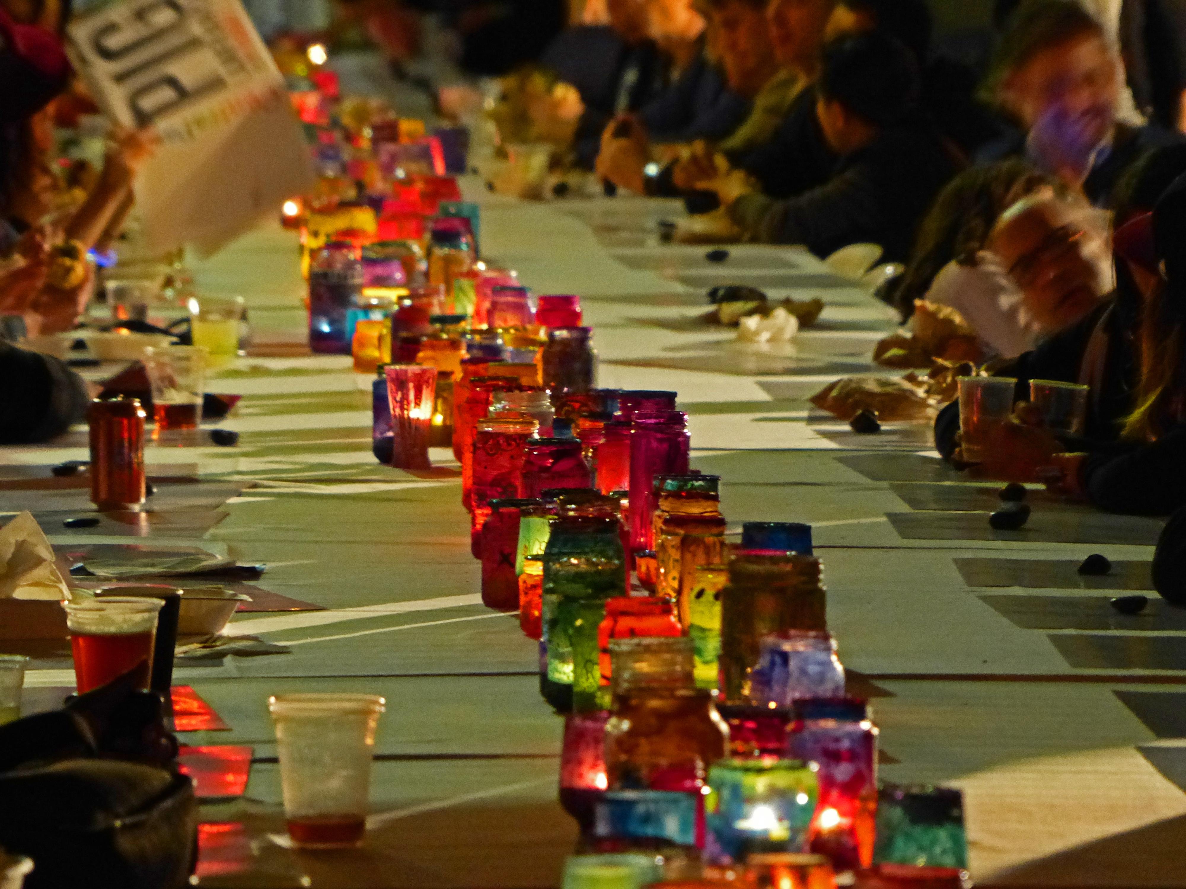 Bunte Gläser mit Teelichtern stehen auf der großen Essenstafel an der Menschen sitzen und essen