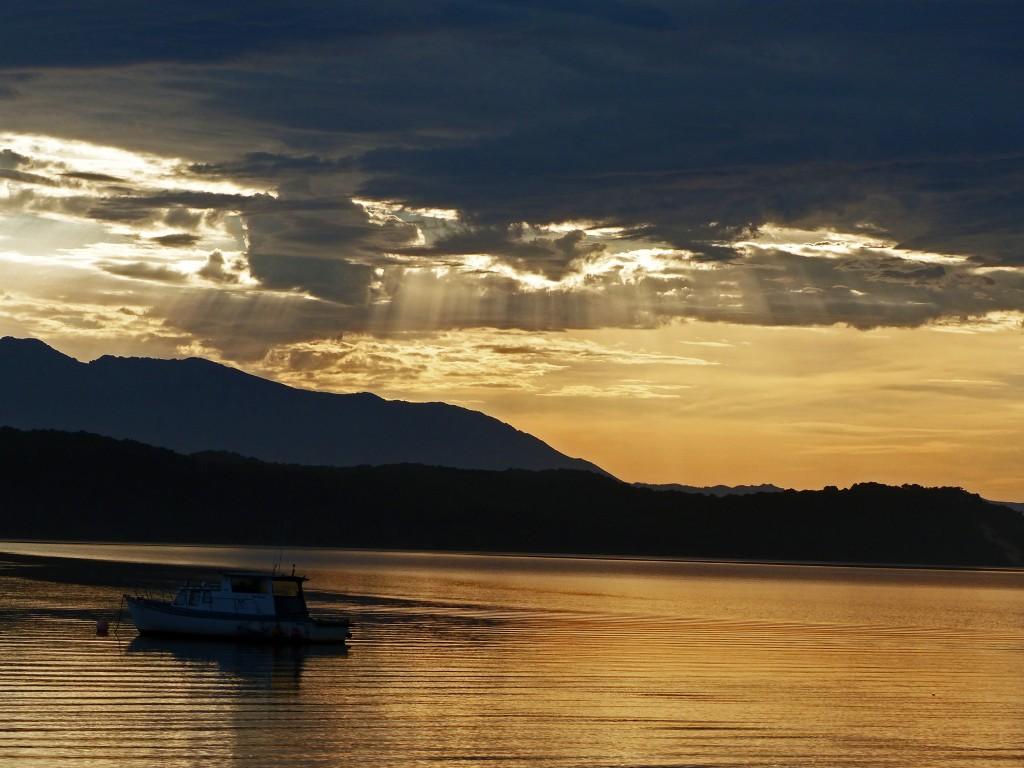 Sonnenaufgang mit Blick auf das Meer und einem ablegenden Fischerboot am Macquarie Heads Campground