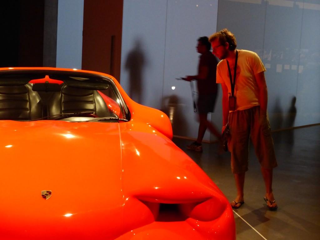 Robert vor einem roten aufgequollenen roten Plastikauto mit Ferraizeichen