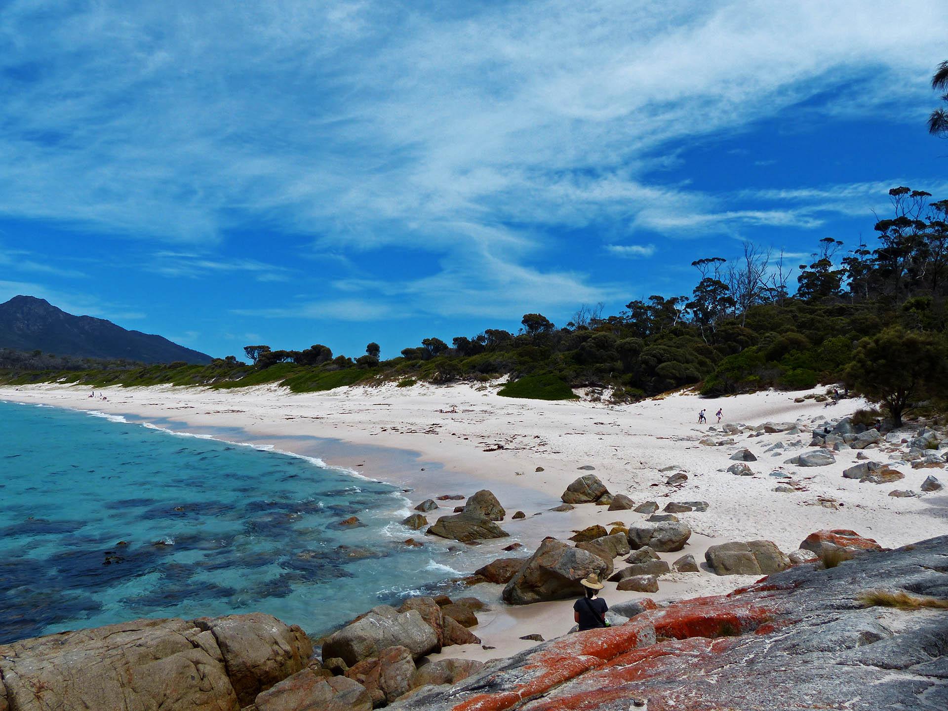 Alina sitzend auf den roten Steinen vor dem Strand an der Wineglass Bay